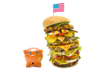 enormous burger falling over on piggy bank