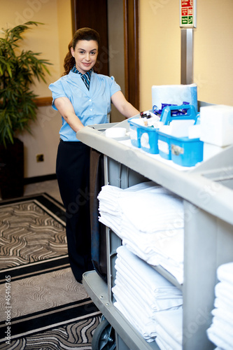 Beautiful employee psuhing housekeeping cart