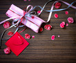 Present,gift bow with petal from flowers on wooden table/