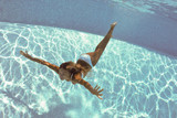 Underwater woman portrait with white bikini in swimming pool.
