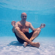 Underwater man in yoga position in a swimming pool