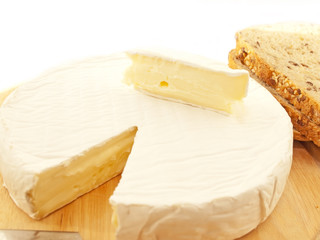 Brie  cheese on wooden desk with knife isolated
