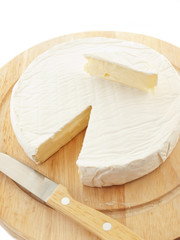Circle Brie  cheese on wooden desk with knife isolated