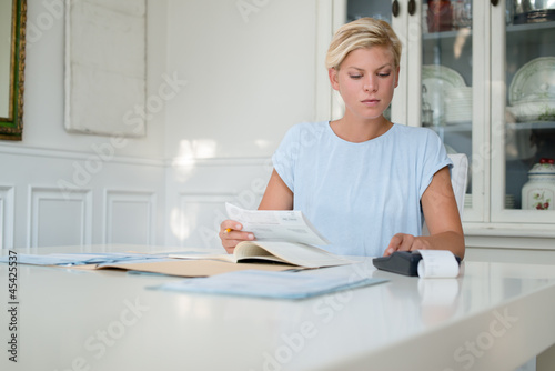 Young woman checking bills and doing budget at home