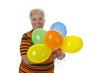 Seniiorin mit bunten Luftballons
