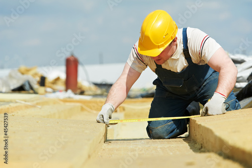 roofer worker measuring insulation material