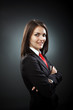 Happy young businesswoman wearing suit and necktie, isolated on