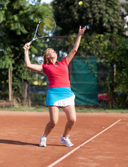 Young woman tennis player serving the ball