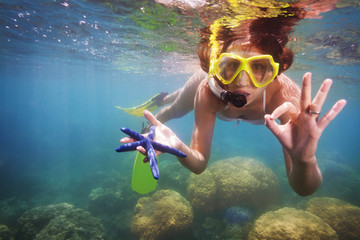 girl in scuba mask holding starfish