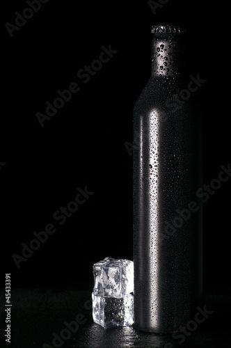 Botella negra fría y cubos de hielo