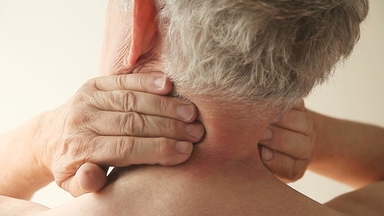 older man tries to rub the stiffness and pain out of his neck