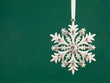 snowflakes pattern bauble hanging over green background