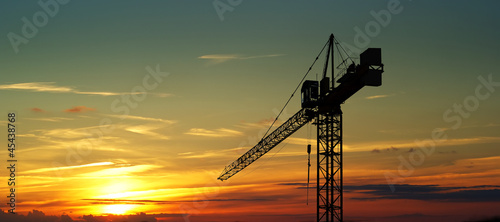 Leinwanddruck Bild Construction crane on sunset