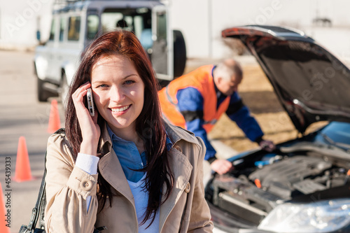 Woman talking on cellphone after car breakdown