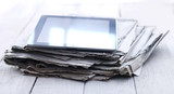 Stack of old newspapers and a tablet pc