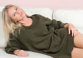 Beautiful tender woman in sweater is posing on a sofa