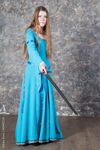 Young woman with long hair poses with sword