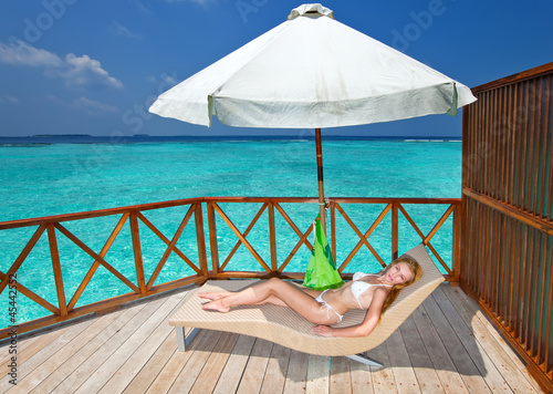 Young woman tans on a water villa terrace , Maldives..