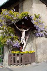 Kreuz Inri Blumen geschmückt lila violett Haus Hauswand