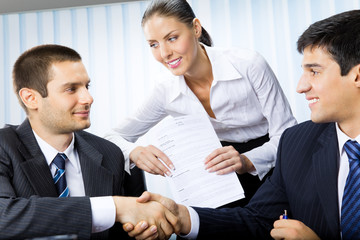 Three businesspeople handshaking with document