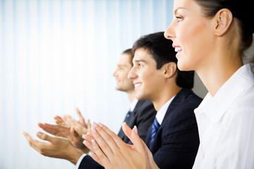 Happy businesspeople applauding at office
