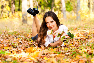woman lying on the autumn leaves with a flower in hand