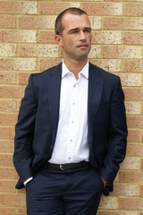 Smartly dressed man posing against a brick wall