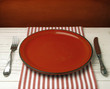 Empty red ceramic plate on white table against red grunge wall