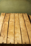 Wooden deck tabletop against grunge wall poster