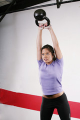 Athletic young woman doing a fitness workout with Kettlebell wei