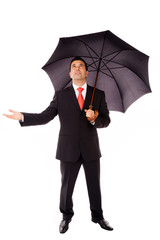 Full body of young business man with umbrella checking if it's r