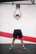 Young man doing kettlebell workout on gym