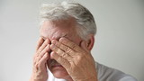fatigued older man rubs his eyes