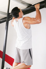 strong man performing pull ups in a bar