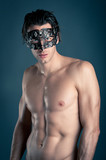 Portrait of young man shirtless with carnival mask