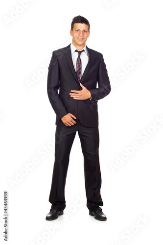 Confident young business man standing against white background