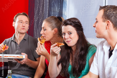 Freunde essen Pizza daheim