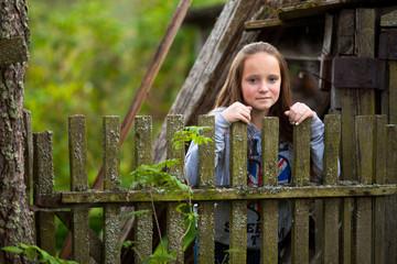 Teen-girl standing near vintage rural fence.