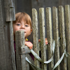Beautiful child standing near vintage rural fence.