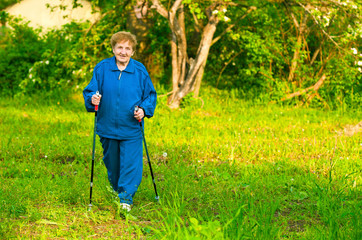 Active old woman (85 years old) nordic walking outdoors.