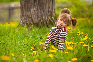 Little lovely girl playing in the park, shows the language