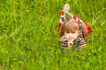 Little five-year girl lying in grass.