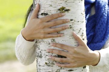 Frau umarmt einen Baum
