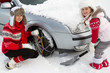 Winter, family putting snow chains onto tyre of car