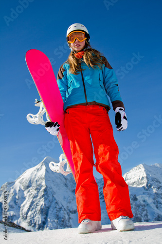Winter vacation - portrait of young snowboarder girl