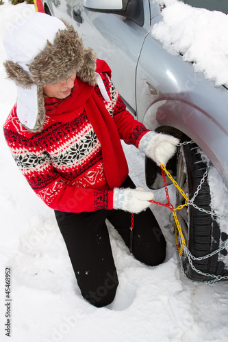 Winter, woman putting snow chains onto tyre of car