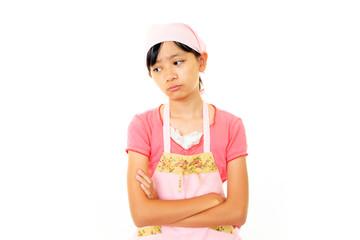 困惑した表情のエプロンを着た女の子