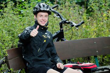 Junger Mountainbiker zeigt Daumen hoch