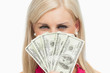 Smiling blonde hiding her face with 100 dollars banknotes
