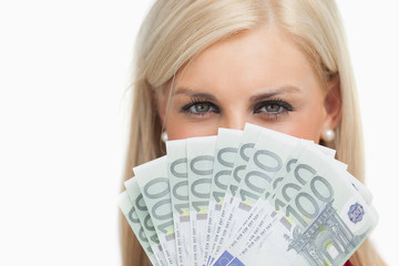 Pretty blonde holding 100 euros banknotes